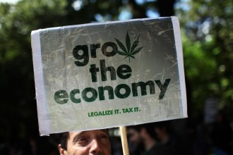 A man holds a poster  while taking part in a march celebrating cannabis culture Saturday, May 7 2011, in Lisbon.  The event was part of the worldwide Global Marijuana March rally held annualy in hundreds of cities. (AP Photo/Armando Franca)