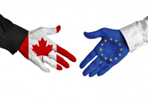 Diplomatic handshake between leaders from Canada and the European Union with flag-painted hands.