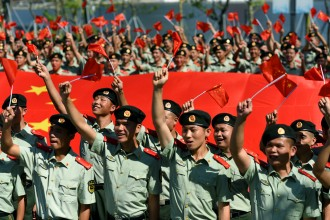 Paramilitary police officers wave Chinese flags during an event marking the upcoming 70th founding anniversary of People's Republic of China in Shenzhen, Guangdong province, China September 20, 2019. Picture taken September 20, 2019. REUTERS/Stringer ATTENTION EDITORS - THIS IMAGE WAS PROVIDED BY A THIRD PARTY. CHINA OUT. - RC17AA56C1E0