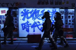 """Riot police in Hong Kong walking past a bus stop graffitied with the slogan """"Liberate Hong Kong, Revolution of Our Times"""". Picture taken on September 29th, 2019, The Atlantic, Vincent Yu / AP"""